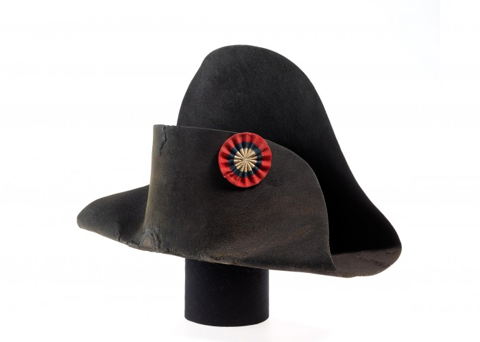 A black bicorne hat with a red, blue and white circular badge on the front