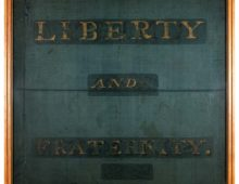 a photo of an old banner with the words Liberty and Fraternity across it