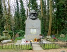 A photograph of the grave of Karl Marx. A large stone plinth is surrounded by flowers, on top of the plinth is a lerge, black statue of the head of Karl Marx.