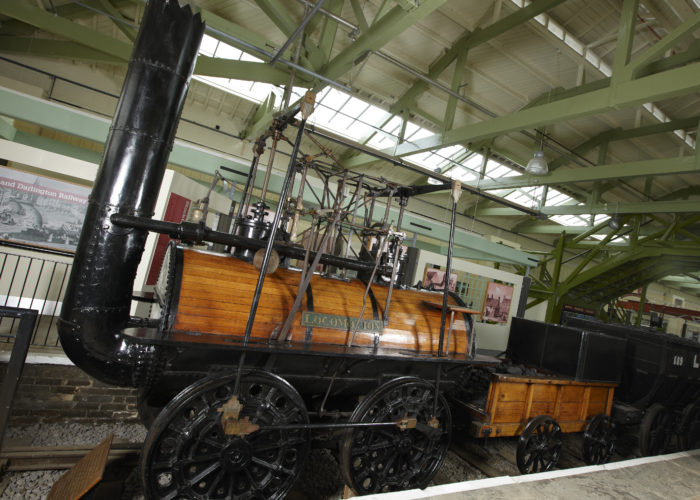A photograph of a large black and wooden steam engine within a museum building