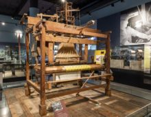 A photograph of a large wooden loom inside a museum building