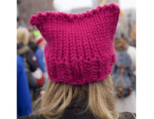 A photograph of a pink knitted hat on a persons head.