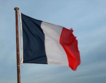 A photograph of the french flag flying in the wind, the far right edge is frayed