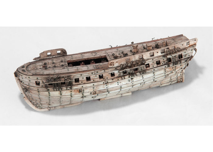 A small model of a boat made of bone.