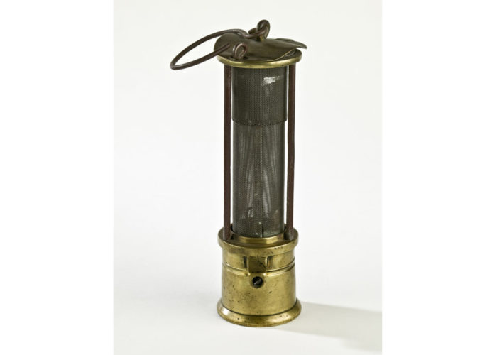 A brass miners lamp with a hook at the top against a white background