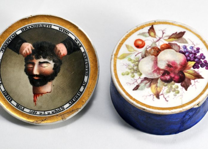 A photograph of a cylindrical ceramic pot showing both the base and the lid of the pot. The exterior base has a painting of a bunch of fruit and flowers within a gilt border. The lid has a painting of a dripping severed head held aloft by two hands. This is surrounded by the legend 'JEREMIAH BRANDRETH WHO WAS EXECUTED AT DERBY NOV.R th 7th 1817 FOR HIGH TREASON'.