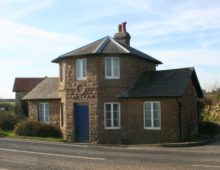 A modern photograph of a tollhouse building on the side of the road. The building is made of stone and has a blue door and white windows