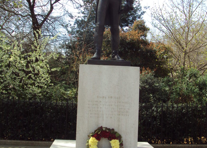 A photograph of a statue in front of a park. The statue is dark brown and shows a man dressed in a formal military uniform. The statue stands on a stone plinth with a wreath of flowers at the bottom. The plinth is engraved with the word 'BOLIVAR'