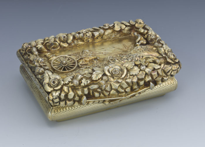 A photograph of a small silver gilt snuffbox with a representation of a coach in the centre of the lid