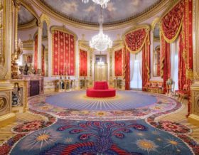 a photo of an opulent room with red and gold decoration and a chandelier