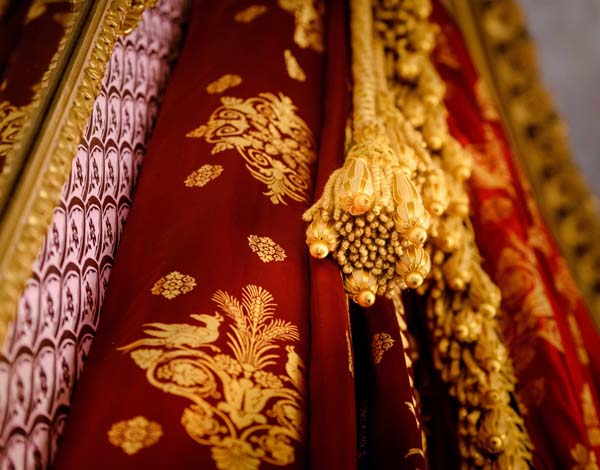 a photo of gold brocade against a red and gold curtain