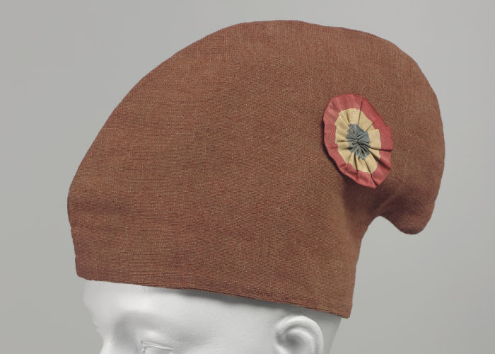 A photograph of a dark orange cap on a manequin head. The cap is hooked at the top and is decorated with a circular, red, white and blue pin.