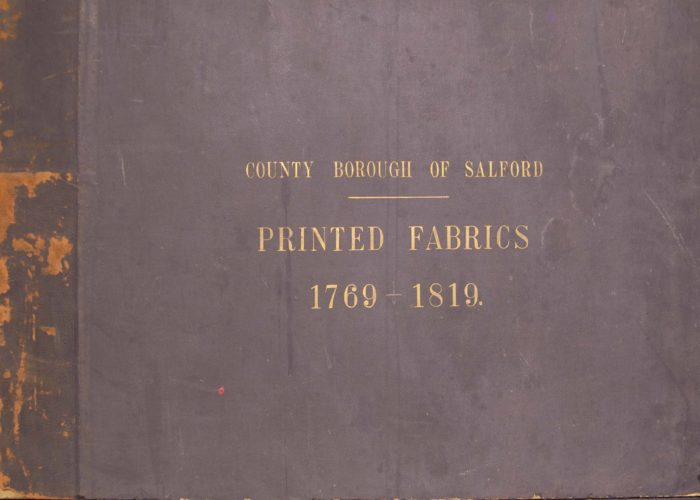 The front cover of a textile sample book from 1769-1819. The cover is blue fabric and is worn on the spine of the book, the lettering is printed in gold.