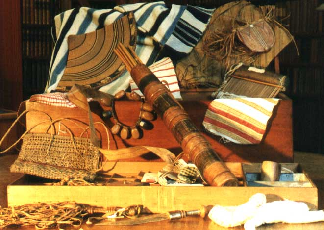 A photograph of a wooden chest with its contents laid out on display. A number of striped fabrics in different colours are draped over the box as well as a beaded necklace. In the foreground a number of trinkets and objects can be seen.