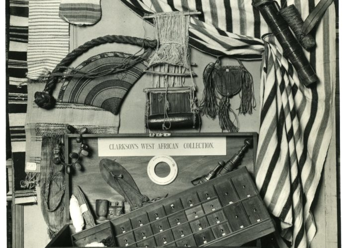 A black and white photograph of a wooden chest with its contents laid out on display. Included in the objects are a number of striped fabrics, a beaded necklace and a sandal, as well as other west African artefacts