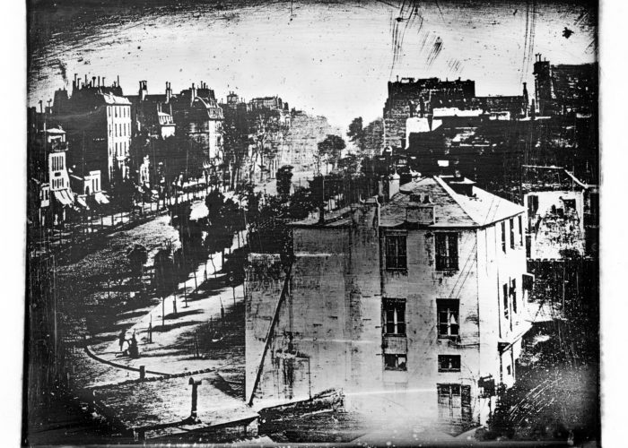 A black and white grainy photograph of a street scene taken from a height. In the bottom left corner a person can be seen having their shoes shined.