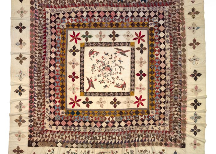 A photograph of a colourful, square quilt decorated with geometric flowers and patterns.