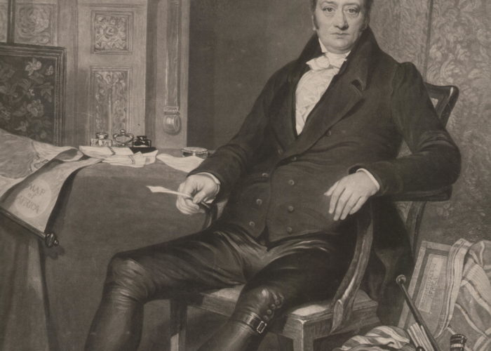 A black and white image of a painting showing a middle-aged man seated in a chair. The man is dressed in formal attire and is surrounded by expensive decoration. At his feet is a wooden chest filled with artefacts from Africa.