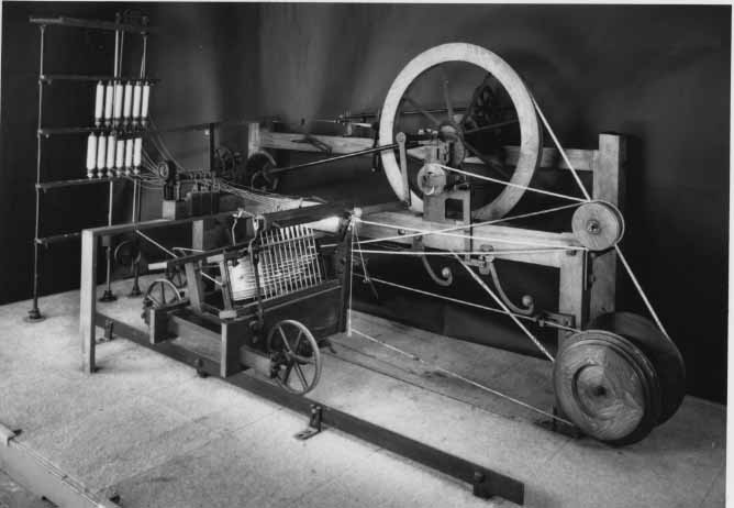A black and white photograph of the spinning mule in action. Cotton threads can be seen stretching between the different wheels of the mechanism.