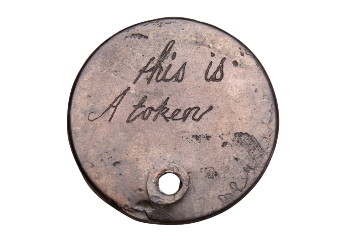 A photograph of a small metal disc against a white background. The disc is engraved with the words 'This is a token'. At the bottom there is a small hole, such that a chain could be passed through to wear the token as a necklace.
