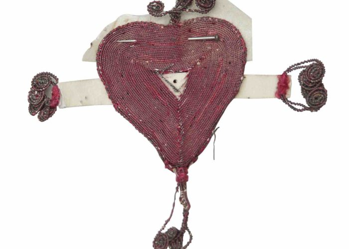 A photograph of a small fabric red heart with a white piece of ribbon pinned behind it. The small token also has beaded details around the heart.