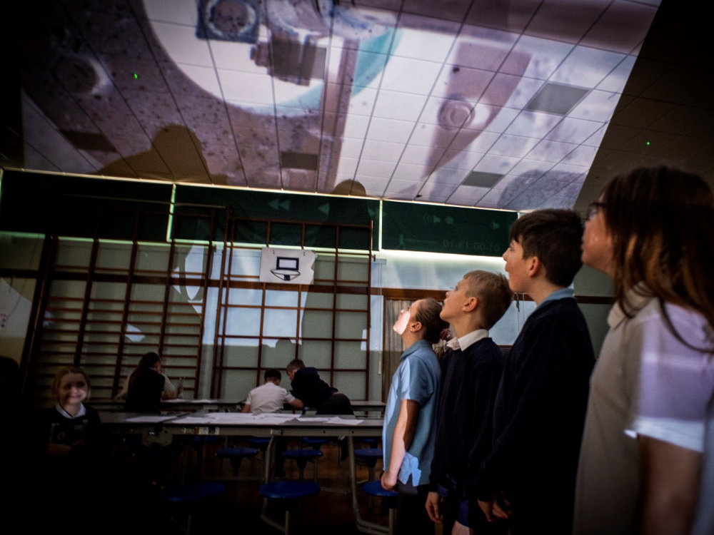 students looking at projection on ceiling