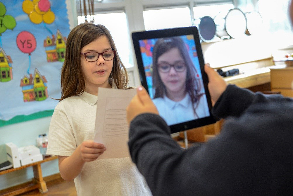 student filming another student on a tablet